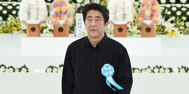 Japanese Prime Minister Shinzo Abe returns his seat after offering a flower at an altar during a memorial service for those who died in the battle of Okinawa during World War II at the Peace Memorial Park in Itoman, Japan's southern islands prefecture of Okinawa, on June 23, 2015. Japan on June 23 marked the 70th anniversary of the end of the Battle of Okinawa, the bloodiest episode in the Pacific War, which killed 200,000 people. AFP PHOTO / Toru YAMANAKA        (Photo credit should read TORU YAMANAKA/AFP/Getty Images)