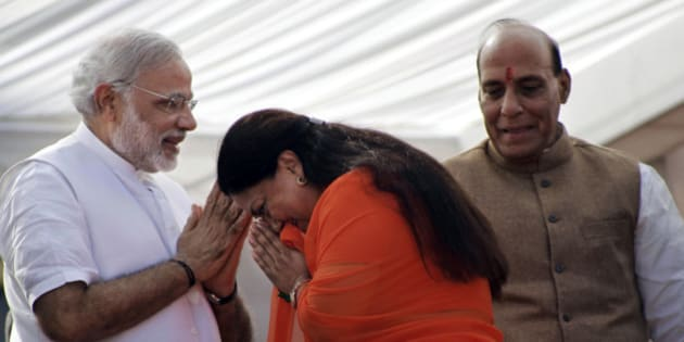 India's main opposition Bharatiya Janata Party (BJP) leader Vasundhara Raje, center, greets party prime ministerial candidate and chief minister of Gujarat state Narendra Modi, left, and party president Rajnath Singh before her oath taking ceremony as the chief minister of Rajasthan state in Jaipur, India, Friday, Dec. 13, 2013. Raje was Friday sworn-in as the chief minister of the state for the second time. (AP Photo/Deepak Sharma)