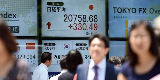 Businessmen walk in front of a securities company window flashing the current Tokyo stock prices in central Tokyo on June 23, 2015. The Nikkei 225 index soared 330.49 points or 1.62 percent to 20,758.68 by the break, breaching 20,700 for the first time since April 2000.     AFP PHOTO / TOSHIFUMI KITAMURA        (Photo credit should read TOSHIFUMI KITAMURA/AFP/Getty Images)