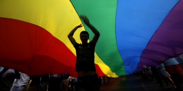 A gay rights activist dances under a rainbow flag during the Gay Pride parade in downtown Athens, on Saturday, June 4, 2011. Around 2000 people took part in the march. (AP Photo/Kostas Tsironis)