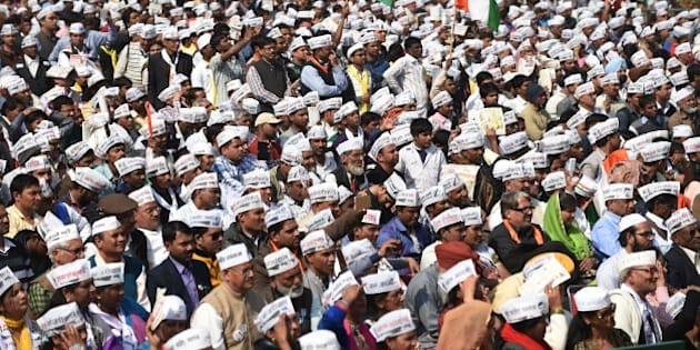 Supporters of the Aam Aadmi Party (AAP) watch as leader Arvind Kejriwal is sworn in as Delhi chief minister by Delhi Lieutenant Governor Najeeb Jung during the ceremony at Ramlila Grounds in New Delhi on February 14, 2015. Arvind Kejriwal promised to makeDelhiIndia's first corruption-free state and end what he called its 'VIP culture' as he was sworn in as chief minister before a huge crowd of cheering supporters.  AFP PHOTO / SAJJAD HUSSAIN        (Photo credit should read SAJJAD HUSSAIN/AFP/Getty Images)