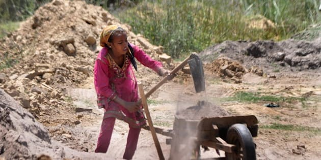 In this photograph taken on June 11, 2015, twelve year old Indian girl, Kavita works at a brick kiln on the outskirts of Jammu on the eve of World Day against Child Labour. World Day against Child Labour is held every year on June 12 and is intended to foster the worldwide movement against child labour in any of its forms.  AFP PHOTO         (Photo credit should read STR/AFP/Getty Images)