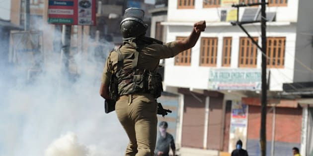 An Indian security personnel throws a rock towards Kashmiri protestors during clashes in Srinagar on April 17, 2015. Police arrested a prominent separatist leader in Indian-administered Kashmir on April 17, 2015 after he led a rally where supporters waved Pakistani flags and chanted pro-Pakistan slogans. Kashmir has been rocked by violent protests after the brother of a top rebel leader was killed by the army near the town of Tral in the south of the Kashmir valley. AFP PHOTO / Tauseef MUSTAFA        (Photo credit should read TAUSEEF MUSTAFA/AFP/Getty Images)