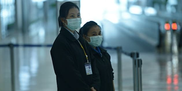 Airports of Thailand employees wear face masks as they wait for travelers to walk past a thermoscan checking their body temperature on arrival at Bangkok's Suvarnabhumi Airport on June 19, 2015.  Thailand on June 18 said a 75-year-old man from Oman was confirmed to have MERS in Southeast Asia's first case of the virus since an outbreak in South Korea that has killed 23 people.   AFP PHOTO / Christophe ARCHAMBAULT        (Photo credit should read CHRISTOPHE ARCHAMBAULT/AFP/Getty Images)