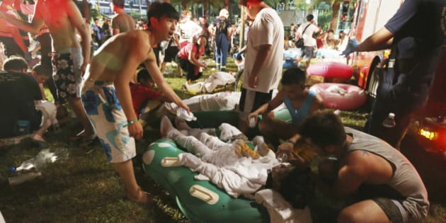 Emergency rescue workers and concert spectators tend to injured victims from an explosion during a music concert at the Formosa Water Park in New Taipei City, Taiwan, Saturday, June 27, 2015. The New Taipei City fire department says 200 people were injured in an accidental explosion of colored theatrical powder Saturday night near a performance stage where about 1,000 people were gathered for party. (AP Photo)    TAIWAN OUT
