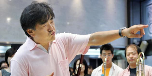 TOKYO, JAPAN:  Japanese Yutaka Sado (C), 44, conducts during his mini concert at a musical instrument store in Tokyo, 26 June 2005, while customers look on. Sado takes over the baton from his late master Leonard Bernstein to conduct memorial concerts in Hiroshima and Nagasaki marking the 60th anniversary of the nuclear bombings and praying for world peace still under threat of terrorism.  AFP PHOTO / Kazuhiro NOGI  (Photo credit should read KAZUHIRO NOGI/AFP/Getty Images)