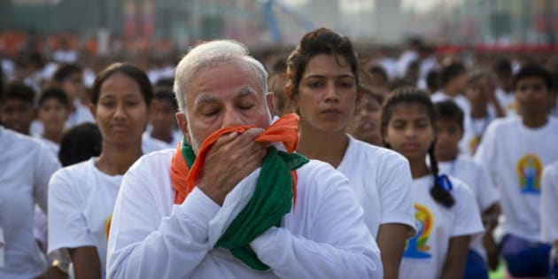 Indian Prime Minister Narendra Modi wipes his sweat with a scarf made in the colors of Indian tricolor as he performs yoga along with thousands of Indians on Rajpath, in New Delhi, India, Sunday, June 21, 2015. Millions of yoga enthusiasts are bending their bodies in complex postures across India as they take part in a mass yoga program to mark the first International Yoga Day.(AP Photo/Saurabh Das)