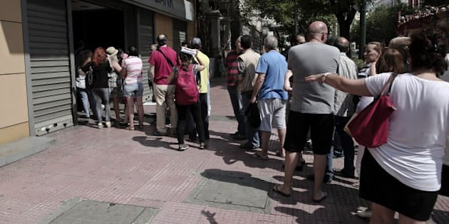 Greeks queue to withdraw cash from an Alpha Bank ATM in central Athens on June 28, 2015. The ECB pledged continued emergency cash for Greece, but no extra help to guard against a feared bank run that could set off financial chaos leading to a euro exit. As the Greek crisis spiralled after talks between Athens and its creditors broke down, Greek citizens have queued at bank machines, heaping pressure on the government to impose capital controls. AFP PHOTO / ANGELOS TZORTZINIS        (Photo credit should read ANGELOS TZORTZINIS/AFP/Getty Images)