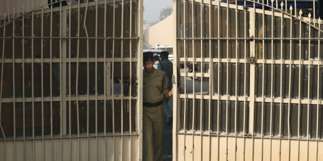 An Indian police officer prepares to close one of the gates at Tihar Jail, the largest complex of prisons in South Asia, in New Delhi, India, Monday, March 11, 2013. Indian police confirmed that Ram Singh, one of the men on trial for his alleged involvement in the gang rape and fatal beating of a woman aboard a New Delhi bus committed suicide at the Tihar jail Monday, but his lawyer and family allege he was killed. (AP Photo/Saurabh Das)