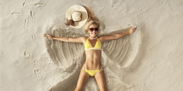 Young attractive woman playfully creating a Sand Angel in the sand on beach.