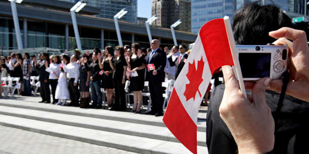 A woman takes a photograph while holding a Canadian flag as a group of 61 new Canadians take the oath of citizenship during a citizenship ceremony held as part of Canada Day celebrations in Vancouver, B.C., on Wednesday July 1, 2009. THE CANADIAN PRESS/Darryl Dyck