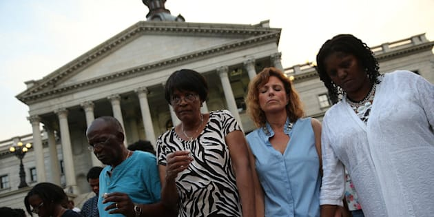 COLUMBIA, SC - JUNE 23:  Participants link arms during a moment of silence at a memorial service for the nine victims of last week's shooting at Emanuel African Methodist Episcopal Church organized by students from the University of South Carolina and South Carolina State University on the grounds of the South Carolina State House June 23, 2015 in Columbia, South Carolina. South Carolina governor Nikki Haley asked that the flag be removed after debate over the flag flying on the capitol grounds was kicked off after nine people were shot and killed during a prayer meeting at the Emanuel African Methodist Episcopal Church in Charleston, South Carolina.  (Photo by Win McNamee/Getty Images)