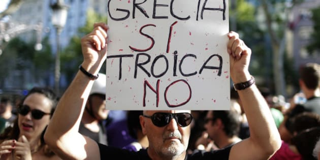 "A man holds a banner during a pro Greece demonstration at the European Union Office in Barcelona, Spain, Monday, June 29, 2015. Spain's economy minister has said a Greek debt deal is still reachable, although Spain's benchmark Ibex stock index slid nearly 4 percent Monday morning. The banner reads in Spanish: ""Greece Yes, Troika No"". (AP Photo/Manu Fernandez)"
