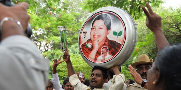 Supporters of All India Anna Dravida Munnetra Kazhagam (AIADMK) supremo, Jayalalithaa Jayaram dance and celebrate as they hear the news of the acquital of their leader in the 18-year-old, disproportionate assets case in Bangalore on May 11, 2015.  The head of India's largest Tamil party was cleared of corruption May 11, 2015, a verdict that sparked wild celebrations by supporters and paved the way for the return of one of the country's most powerful politicians.     AFP PHOTO/ Manjunath KIRAN        (Photo credit should read Manjunath Kiran/AFP/Getty Images)