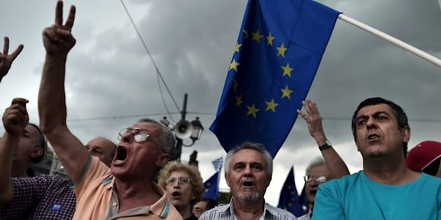 Pro-euro protesters hold European Union flags during a demonstration in front of the parliament in Athens on June 30, 2015. European leaders want to 'sink' Greece's ruling Syriza party to block the rise of other far-left, anti-austerity parties such as Podemos in Spain, Greece's Labour Minister Panos Skourletis said Tuesday. AFP PHOTO /  ARIS MESSINIS        (Photo credit should read ARIS MESSINIS/AFP/Getty Images)