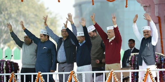 Aam Aadmi Party (AAP) president Arvind Kejriwal (C) and fellow AAP ministers Sandeep Kumar, (L), Asim Ahmed Khan (2L), Satyendra Jain (3L), Gopal Rai, (3R), Manish Sisodia (2R) and Jitender Singh Tomar (R) greet supporters during his swearing-in ceremony as Delhi chief minister in New Delhi on February 14, 2015.  Arvind Kejriwal promised to make Delhi India's first corruption-free state and end what he called its 'VIP culture' as he was sworn in as chief minister before a huge crowd of cheering supporters .   AFP PHOTO / PRAKASH SINGH        (Photo credit should read PRAKASH SINGH/AFP/Getty Images)