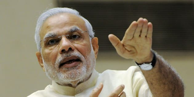 Indian Prime Minister Narendra Modi gestures as he addresses a ceremony at the launch of 'Smart Cities Mission, Atal Mission for Rejuvenation and Urban Transformation (AMRUT)' in New Delhi on June 25, 2015. AFP PHOTO/STR        (Photo credit should read STRDEL/AFP/Getty Images)
