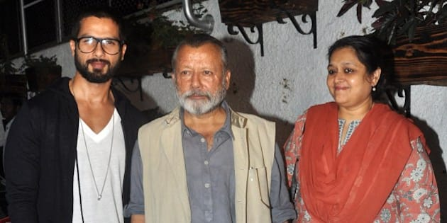 Indian Bollywood actor Shahid Kapoor (L) and his father, actor and director Pankaj Kapoor (C) and his mother, Bollywood actress Supriya Pathak pose for a photograph during a screening of Sri Lankan film Inam, written, directed and produced by Santosh Sivan (L) in Mumbai on late March 26, 2014. AFP PHOTO / STR        (Photo credit should read STRDEL/AFP/Getty Images)
