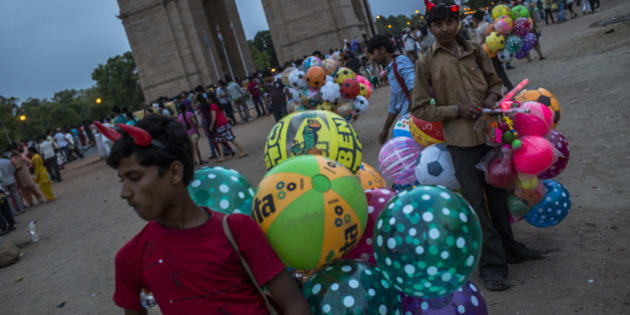 NEW DELHI, INDIA - JUNE 02: Boys selling balloons wait for customers at the India Gate monument on June 2, 2012 in New Delhi, India. A Heat wave continues across the Northern India capital and expects to remain above 40 degrees celsius all week. (Photo by Daniel Berehulak /Getty Images )