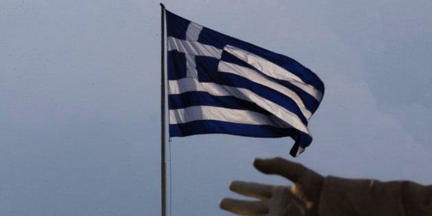 A hand of a statue is seen as the Greek flag waves in Athens, Sunday, June 28, 2015. Greek Prime Minister Alexis Tsipras says the Bank of Greece has recommended that banks remain closed and restrictions be imposed on transactions, after the European Central Bank didn't increase the amount of emergency liquidity the lenders can access from the central bank. (AP Photo/Daniel Ochoa de Olza)