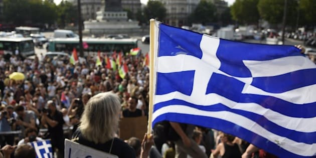 A protester holds a Greek flag as she takes part in a rally in support of the people of Greece at the 'Place de la Bastille' in Paris on July 2, 2015, as Greeks prepare to vote in a referendum on bailout conditions on July 5. AFP PHOTO / LOIC VENANCE        (Photo credit should read LOIC VENANCE/AFP/Getty Images)