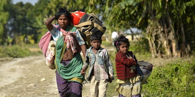 Indian villagers carry their belongings as they flee from the village of Tenganala in Sonitpur District, some 250kms east of Guwahati on December 24, 2014, after their relatives were killed by militants.   Violence in the restive Indian state of Assam has killed 68 people including 12 children, authorities said, as separatist rebels dramatically intensified a long-running campaign in the tea-growing area.  Heavily armed militants launched a series of coordinated attacks in rural Assam late December 22, pulling villagers from their homes and shooting them at point-blank range, witnesses said.   AFP PHOTO/STR        (Photo credit should read STRDEL/AFP/Getty Images)