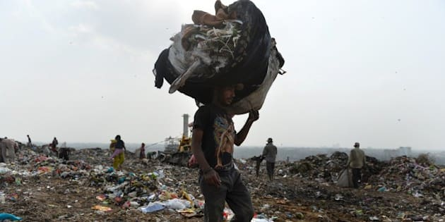 An Indian rag picker carries a sack of sorted recyclable materials at the Ghazipur landfill site in the east of New Delhi on August 19, 2014.  The population of New Delhi, which is predicted to reach close to 21 million by the year 2015, generates 8,000 tons of garbage per day.   The trash is not separated between organic and inorganic materials - everything from leftover food to batteries and beverage cans goes into Indian bins - hurting efficiency and raising toxic emissions.     AFP PHOTO/Chandan Khanna        (Photo credit should read Chandan Khanna/AFP/Getty Images)