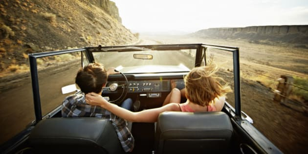 Young couple driving convertible off road vehicle at sunset on desert road