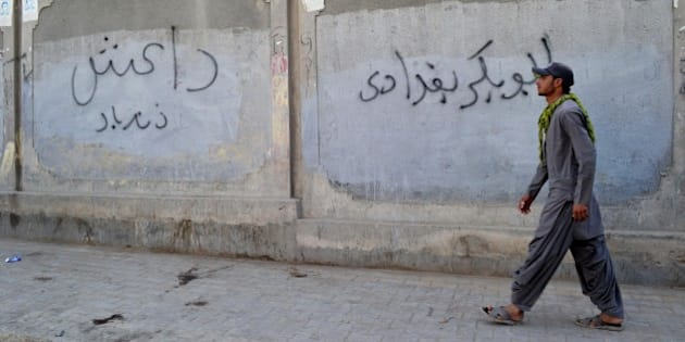 A Pakistani man walks past a wall graffiti reading 'Abu Bakr al-Baghdadi', leader of the Islamic State (IS) jihadist group in Iraq, in Quetta on November 24, 2014. The Islamic State organisation is starting to attract the attention of radicals in Pakistan and Afghanistan, long a cradle for Islamist militancy, unnerving authorities who fear a potential violent contagion. AFP PHOTO/Banaras KHAN        (Photo credit should read BANARAS KHAN/AFP/Getty Images)