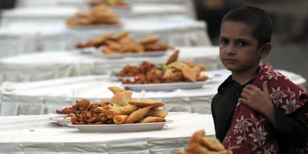 A Pakistani boy stands beside Iftar food to break their Ramadan fast on a street in Karachi on July 3, 2015. Ramadan is marked by Muslims worldwide and implies fasting, abstaining from foods, sex and smoking from dawn to dusk. AFP PHOTO / Rizwan TABASSUM        (Photo credit should read RIZWAN TABASSUM/AFP/Getty Images)