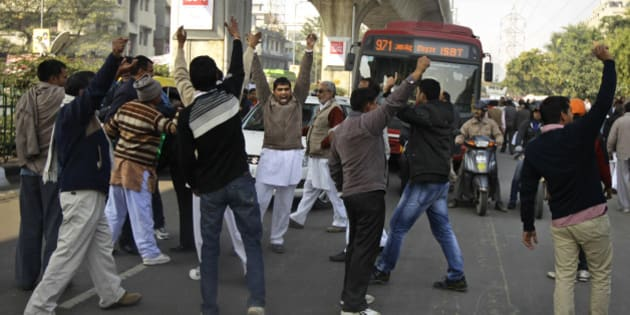 Supporters of former Haryana state Chief Minister Om Prakash Chautala stop traffic and shout slogans outside a court in New Delhi, India, Tuesday, Jan. 22, 2013. According to local news reports, a Delhi court Tuesday sentenced Chautala and his son Ajay Chautala to 10 years imprisonment for corruption in a teachers' recruitment scam and other charges amidst scenes of violence by his supporters. (AP Photo/Altaf Qadri)