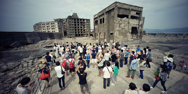 """In this June 29, 2015 photo, tourists visit a part of Hashima Island, commonly known as Gunkanjima, which means """"Battleship Island,"""" off Nagasaki, Nagasaki Prefecture, southern Japan.  The island is one of 23 old industrial facilities seeking UNESCO's recognition as world heritage """"Sites of Japan's Meiji Industrial Revolution"""" meant to illustrate Japan's rapid transformation from a feudal farming society into an industrial power at the end of the 19th century. UNESCO's World Heritage Committee is expected to approve the proposal during a meeting being held in Bonn, Germany, through July 9. (AP Photo/Eugene Hoshiko)"""