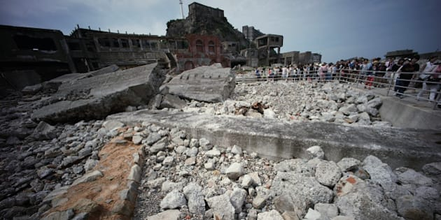 "In this June 29, 2015 photo, forlorn buildings are seen at Hashima Island, commonly known as Gunkanjima, which means ""battleship island,"" off Nagasaki, Nagasaki Prefecture, southern Japan.  The island is one of 23 old industrial facilities seeking UNESCO's recognition as world heritage ""Sites of Japan's Meiji Industrial Revolution"" meant to illustrate Japan's rapid transformation from a feudal farming society into an industrial power at the end of the 19th century. UNESCO's World Heritage Committee is expected to approve the proposal during a meeting being held in Bonn, Germany, through July 9.   (AP Photo/Eugene Hoshiko)"