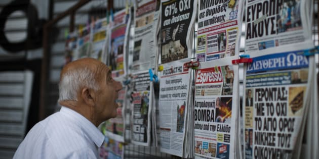 """A man looks at the newspapers at a newsstand in central Athens, Monday, July 6, 2015. Greece's finance minister has resigned following Sunday's referendum in which the majority of voters said """"no"""" to more austerity measures in exchange for another financial bailout. (AP Photo/Emilio Morenatti)"""