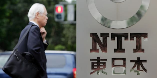 A man walks by a corporate sign of Nippon Telegraph and Telephone (NTT) East Corp. at its headquarters in Tokyo Tuesday May 13, 2008. Japan's top telecommunications company NTT Corp. said Tuesday its group net profit surged 32 percent for the fiscal 2007 on booming long distance and international communications business. (AP Photo/Koji Sasahara)