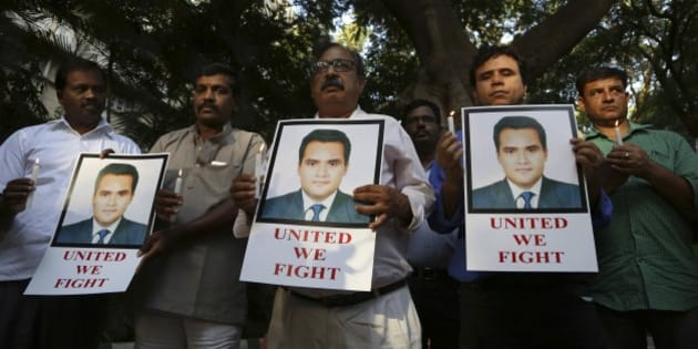 """Indian journalists hold candles and photographs of Akshay Singh during a memorial meeting in Bangalore, India, Monday, July 6, 2015. Singh, an Indian television journalist died under mysterious circumstances Saturday while on assignment covering allegations of a massive scheme to manipulate the results of entrance examinations for government jobs and medical colleges in the central Indian state of Madhya Pradesh. The alleged scam labeled """"Vyapam"""" by Indian media after the Hindi name of the state's professional examination board since the story first surfaced in 2013. (AP Photo/Aijaz Rahi)"""