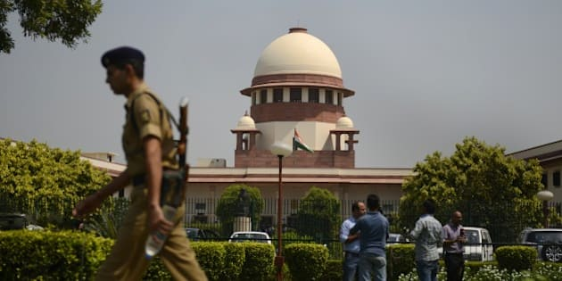 A security personel walks in front of the Indian Supreme court in New Delhi on August 27, 2014.  India's top court said lawmakers with criminal backgrounds should not serve in government, with 13 ministers facing charges for attempted murder, rioting and other offences. The ruling is likely to put pressure on right-wing Prime Minister Narendra Modi, who swept to power this year pledging clean governance.    AFP PHOTO/ SAJJAD HUSSAIN        (Photo credit should read SAJJAD HUSSAIN/AFP/Getty Images)