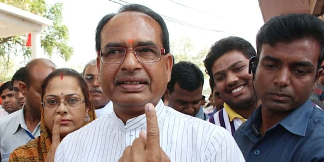 Chief Minister of the central Indian state of Madhya Pradesh Shivraj Singh Chouhan (C) poses with his wife Sadhna Singh (L) as they show their inked-fingers after casting their votes in anational elections in the village of Jait, some 70kms from Bhopal on April 24, 2014.   India's 814-million-strong electorate is voting in the world's biggest election which is set to sweep the Hindu nationalist opposition to power at a time of low growth, anger about corruption and warnings about religious unrest.  AFP PHOTO/STR        (Photo credit should read STRDEL/AFP/Getty Images)