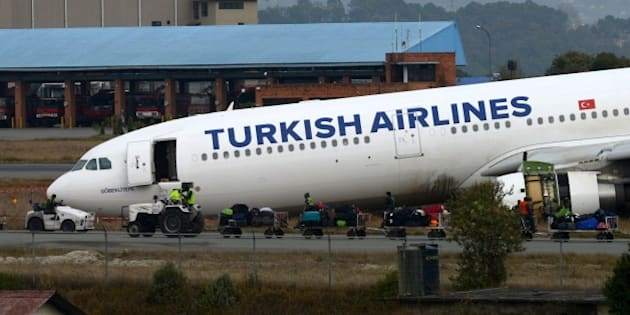 Airline workers move passenger luggage from a Turkish Airlines plane after it slid off the tarmac at Kathmandu international airport on March 4, 2015.  A Turkish Airlines plane carrying 224 passengers had to be evacuated after it missed the runway on landing at Kathmandu airport and skidded onto nearby grassland.  AFP PHOTO / PRAKASH MATHEMA        (Photo credit should read PRAKASH MATHEMA/AFP/Getty Images)