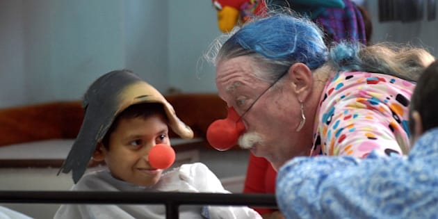 Dr. Hunter Patch Adams talks with a boy on a hospital bed at a public pediatric hospital in Panama City, Panama, Wednesday, Nov. 29, 2006. Adams is on tour in Panama visiting public clinics and giving lectures to medical students. (AP Photo/Tito Herrera)