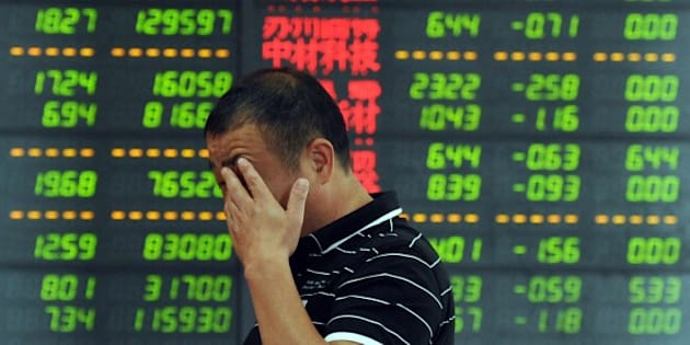 An investor reacts in front of a screen showing stock market movements in Fuyang, eastern China's Anhui province. Chinese shares took another tumble on July 7, defying government efforts to arrest a precipitous fall that has wiped an estimated $3.2 trillion off markets and threatens the world's number-two economy. AFP PHOTO   CHINA OUT        (Photo credit should read STR/AFP/Getty Images)