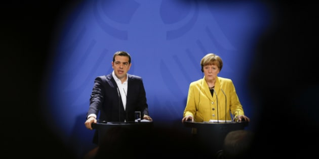 In this photo taken with the silhouette of a television camera in the foreground, German Chancellor Angela Merkel, right, and the Prime Minister of Greece Alexis Tsipras brief the media during a bilateral meeting with at the chancellery in Berlin, Monday, March 23, 2015. (AP Photo/Markus Schreiber)
