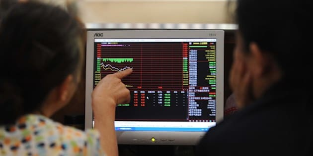 Investors talk to each other as they check stock prices at a securities firm in Wuhan, in central China's Hubei province on July 3, 2015. Shanghai shares on July 3 extended their plunges of recent weeks, ending the morning session down more than three percent in volatile trading as analysts said panic was setting in.     CHINA OUT   AFP PHOTO        (Photo credit should read STR/AFP/Getty Images)