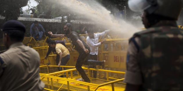 """Police use water canon to disperse activists of India's Congress party's youth wing as they protest against Shivraj Singh Chauhan, chief minister of the central Indian state of Madhya Pradesh, in New Delhi, India, Wednesday, July 8, 2015. Protests against Chauhan and his administration has peaked in recent days after several witnesses in a case alleging a massive scheme to manipulate the results of entrance examinations for government jobs and medical colleges in Madhya Pradesh died under mysterious circumstances. The alleged scam has been labeled """"Vyapam"""" by Indian media after the Hindi name of the state's professional examination board since the story first surfaced in 2013. (AP Photo/Tsering Topgyal)"""
