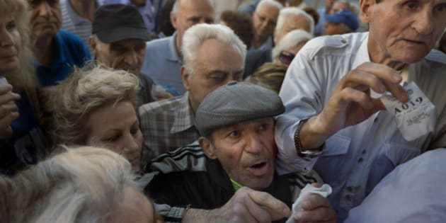 Pensioners holding their queue numbers try to enter into a bank in Athens, Wednesday, July 1, 2015. About 1,000 bank branches around the country were ordered by the government to reopen Wednesday to help desperate pensioners without ATM cards cash up to 120 euros ($134) from their retirement checks. Eurozone finance ministers were set to weigh Greece's latest proposal for aid Wednesday. (AP Photo/Daniel Ochoa de Olza)