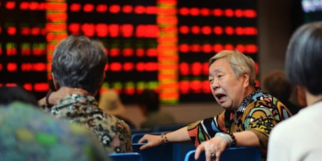 A stock investor reacts in front of a screen showing stock market movements in a brokerage house in Shanghai on July 6, 2015.  Shanghai stocks were up 2.15 percent at midday on July 6 after the government unveiled its biggest package of measures so far to shore up the slumping market, but an initial surge was pared as analysts questioned their effect.   AFP PHOTO / JOHANNES EISELE        (Photo credit should read JOHANNES EISELE/AFP/Getty Images)