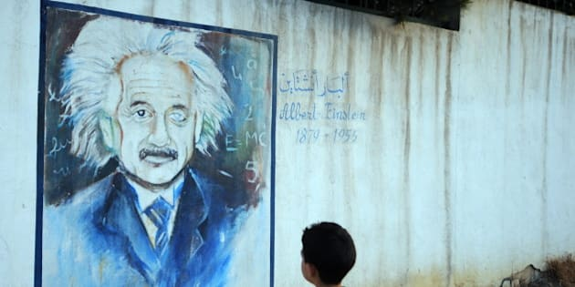 A boy looks at a wall showing a graffiti painting of Albert Einstein in Tunis, on July 11, 2010. AFP PHOTO / FETHI BELAID (Photo credit should read FETHI BELAID/AFP/Getty Images)