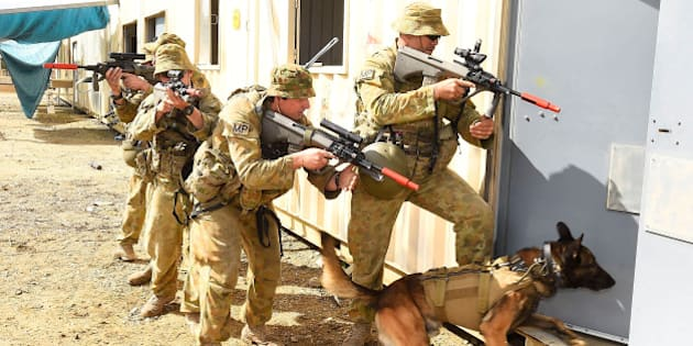ROCKHAMPTON, AUSTRALIA - JULY 09:  Australian soldiers from the 1st Military Police Battalion conduct a breach in an urban environment as part of exercise Talisman Sabre on July 9, 2015 in Rockhampton, Australia. Talisman Sabre is a biennial military exercise that trains Australian and U.S. forces to plan and conduct combined task force operations to improve combat readiness and interoperability on a variety of missions from conventional conflict to peacekeeping and humanitarian assistance efforts. TS15 will incorporate force preparation activities, Special Forces activities, amphibious landings, parachuting, land force manoeuvre, urban operations, air operations, maritime operations and the coordinated firing of live ammunition and explosive ordnance from small arms, artillery, naval vessels and aircraft.  (Photo by Ian Hitchcock/Getty Images)
