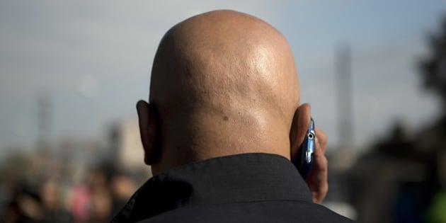 A police officer speaks by mobile outside the cemetery where  'Don Diego', father of Argentina's former football star Diego Armando Maradona, is being buried in Buenos Aires,  outskirts of Buenos Aires, on June 26, 2015.  Don Diego passed away on Thursday,  with the 87-year-old failing to recover from long-standing coronary and respiratory difficulties. AFP PHOTO/EITAN ABRAMOVICH        (Photo credit should read EITAN ABRAMOVICH/AFP/Getty Images)