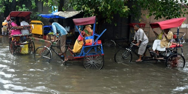 Indian cycle rickshaw drivers ferry commuters through floodwaters on a street of New Delhi on July 9, 2015, after heavy monsoon rainfall. AFP PHOTO/MONEY SHARMA        (Photo credit should read MONEY SHARMA/AFP/Getty Images)